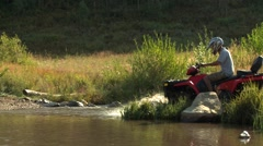 Riders riding all terrain vehicle on dirt track Stock Footage