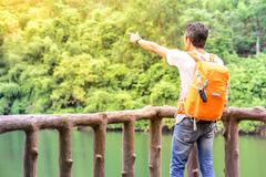 Man hiker in blue jean with orange backpack pointing and looking view of rive Stock Photos