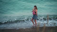 Mother and a baby girl walking on the beach Stock Footage
