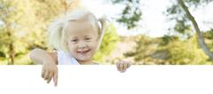 Cute Little Girl Outside Holding Edge of White Board with Room For Text. - stock photo