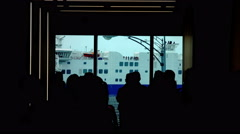 People in Silhouette Waiting the Boarding of a Ferryboad Approching Stock Footage