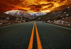 Beautiful sun rising sky with asphalt highways road against  snow mountain sc Kuvituskuvat
