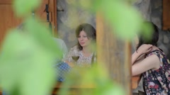Two young couples sitting, talking, laughing and enjoying some food and drinks - stock footage