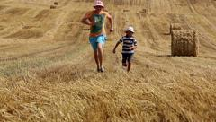 Father and son running on the field near the haystacks, mown field Stock Footage