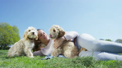 4K Woman relaxing in the park with 2 cute young cocker-poo puppies Stock Footage