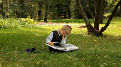 Boy studying encyclopedia Outdoors - stock footage