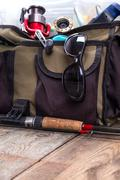 fishing tackles and lures in open handbag - stock photo