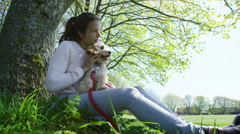 4K Woman relaxing in the park with cute young cocker-poo puppy.  - stock footage