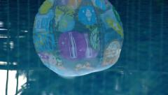 Ball reflection floats across swimming pool Stock Footage