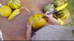 Over shoulder view of drawing pumpkin face 4K Stock Footage