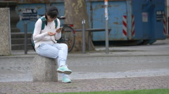 Girl sitting on the sidewalk of a street and searching on her phone, Stuttgart Stock Footage