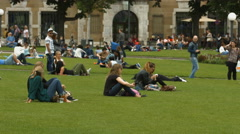 Tourists relaxing and sitting on grass in Palace Square, Stuttgart Stock Footage