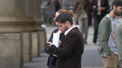 Man searching on mobile phone and showing directions in Palace Square, Stuttgart Stock Footage