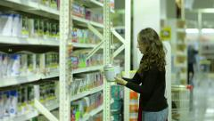 Stock Video Footage of Young Woman Choose The Paint In The Store