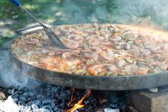 Preparing paella in large pan Stock Photos
