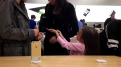 Woman playing new iphone 6s inside Apple store Stock Footage