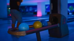 Caucasion woman picks up bowling ball - neon Stock Footage