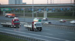 Two lorries driving on the highway. Camera tracking Stock Footage