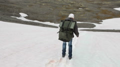 Hiker sliding down the slope on the legs, snow covered mountain pass Stock Footage