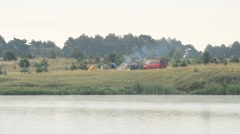 Smoke from fire in camp with tents and car on river bank Stock Footage