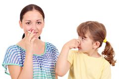 little girl bothered by tobacco smoke - stock photo