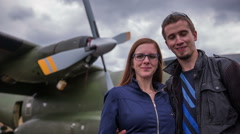 Couple take selfie photo in front of big army aircraft Stock Footage