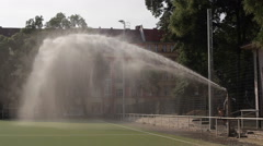 Children run and play in water canon sprinkler on hot summer day Stock Footage