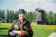 Russian woman in traditional Russian dress and scarf on the back Stock Photos