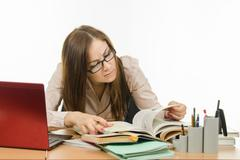 Teacher reading something in a textbook - stock photo