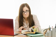 Frustrated teacher is looking for something in a book - stock photo