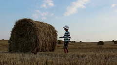 Boy stands near haystack and makes a straw Stock Footage