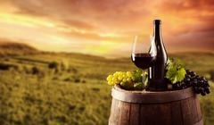 Red wine bottle and glass on wodden keg Stock Photos