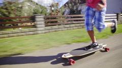 Boy long boarding through neighbourhood 4K Stock Footage