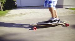 Longboarder speeding on street close up Stock Footage