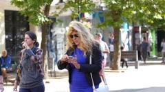 Woman walking on pedestrian street watching her smart phone screen Arkistovideo