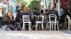 People relax sitting eating in a street cafe on a pedestrian city center Stock Footage