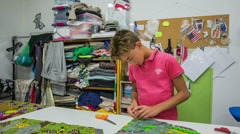 Young boy working in tailor shop Stock Footage
