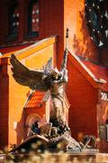 Statue Of Archangel Michael near Red Catholic Church Of St. Simo Stock Photos