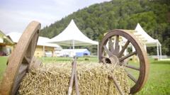Two wooden wheels lean on hay jib shot 4K Stock Footage
