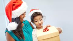 happy mother and child in santa hats with gift box - stock photo