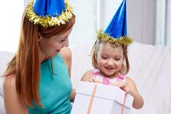 happy mother and child in party caps with gift box - stock photo
