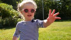 Young girl waving and smiling Stock Footage