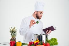 Male chef cook reading recipe book while preparing food - stock photo