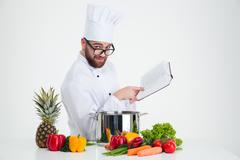 Male chef cook in glasses holding receipe book - stock photo