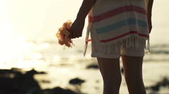 Young woman standing with flower close to the sea during sunset 240 fps HD Stock Footage