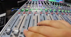 Wide angle shot of an audio mixer and a man pulling up the knobs - stock footage