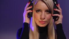 Young girl putting headphones on - stock footage