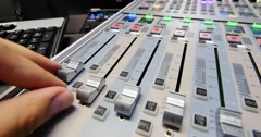 A colorful audio mixer, the knobs are being pulled up by a technician Stock Footage