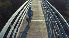 A woman biking over tall wood bridge Stock Footage