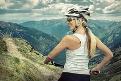 Stock Photo of Beautiful woman in helmet and glasses stay on the bicycle around
